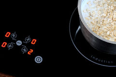 Induction stove, pot metal on it. Royalty Free Stock Photography