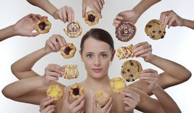 Indulge yourself. Woman surrounded by many hands holding cream cakes with so much choice and temptation is she going to forget about her diet and indulge herself royalty free stock images
