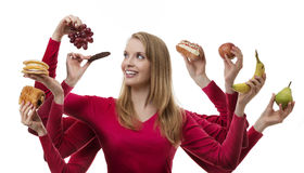Indulge yourself. Woman with eight arms holding fruit and cakes in each hand royalty free stock images