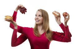 Indulge yourself. Woman with four arms holding fruit and cakes in each hand stock photo