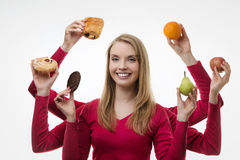 Indulge yourself. Woman with six arms holding cake and fruit not sure what to eat royalty free stock images