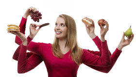 Indulge yourself. Woman with six arms holding fruit and cakes in each hand stock photography