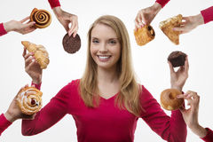 Indulge yourself. Young woman surrounded by many cakes royalty free stock photography