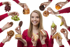 Indulge yourself. Young woman surrounded my many cakes and fruits not sure what to eat stock images