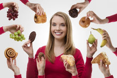 Indulge yourself. Young woman surrounded my many cakes and fruits not sure what to eat royalty free stock image