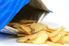 Indulgence. Potato chips spilling from bag Royalty Free Stock Photo