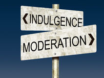 Indulgence VS. Moderation Tin Road Signs Stock Photo