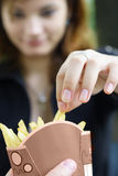Indulging in french fries  Royalty Free Stock Photos