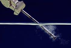 Indurisca il chiodo d'acciaio in acqua blu Fotografie Stock Libere da Diritti