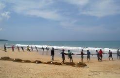 INDURUWA, SRI LANKA - 26 APRILE 2013: I pescatori dello Sri Lanka tirano la grande rete in Induruwa, Sri Lanka La pesca è un'occu Fotografia Stock Libera da Diritti