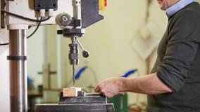 Industriële boringsmachine - een mensenarbeider maakt gaten in metaalplaat royalty-vrije stock afbeeldingen