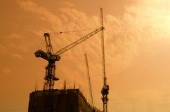Industriële bouwkranen en de bouwsilhouetten over zon Royalty-vrije Stock Foto's