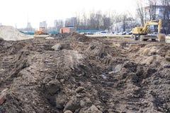Industriële faciliteit over gegraven bouwwerf, gevaar er is een tractor met een emmer royalty-vrije stock fotografie