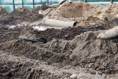 Industriële faciliteit over gegraven bouwwerf, gevaar er is een tractor met een emmer stock afbeeldingen