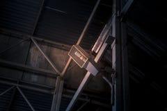 Industriële gloeilamp in een beschermende draadkooi, opgezet bij de metaalmuur stock afbeeldingen