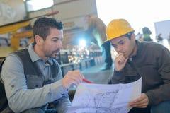 Industriële ingenieur die plan tonen aan manager royalty-vrije stock afbeeldingen