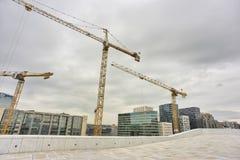 Industriële kranen die de stadsachtergrond bouwen van Oslo Royalty-vrije Stock Afbeeldingen