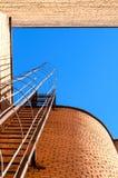 Industriële ladder, blauwe hemel en bakstenen muren van het gebouw Stock Afbeeldingen
