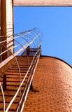 Industriële ladder, blauwe hemel en bakstenen muren van het gebouw Stock Foto