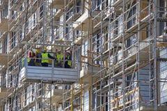 Industriële lift voor de hoge bouw met bouwvakkers Stock Fotografie