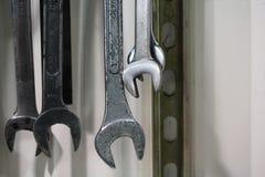 Industriële macro die van metaalmoersleutels wordt geschoten die op muur hangen Stock Afbeeldingen