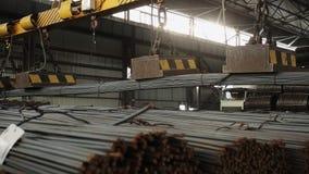 Industriële magneet die staalbars binnen het wijd geschotene pakhuis plaatsen stock footage