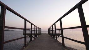 Industriële metaalhandvatten en een weg aan het overzees tijdens een zonsondergang in Riga, Letland stock footage