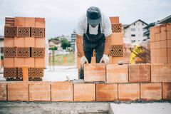 industriële metselaar die bakstenen installeren op bouwbouwterrein stock fotografie