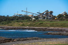 Industriële raffinaderij of bouwmaterialenwerf door de oceaan Royalty-vrije Stock Afbeelding