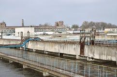 Industriële ruimte met veel pijpen en mededelingen over een achtergrond van blauwe hemel oude waterzuiveringsinstallatie op het s royalty-vrije stock foto's