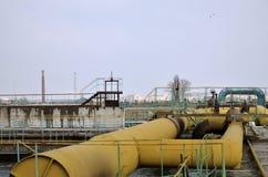 Industriële ruimte met veel pijpen en mededelingen over een achtergrond van blauwe hemel oude waterzuiveringsinstallatie op het s stock foto