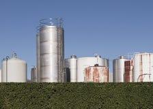 Industriële tanks achter haag royalty-vrije stock afbeelding