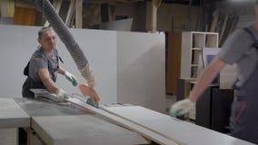 Industriële timmermansarbeiders die aan scherpe houten machine werken stock videobeelden