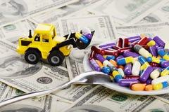 Industriële tractorstuk speelgoed ladingspillen en tabletten aan plaat Stock Foto