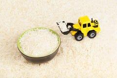 Industriële tractorstuk speelgoed ladingsrijst aan plaat Stock Foto's