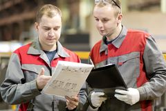 Industriële verwerkende arbeiders die techniektekening lezen royalty-vrije stock afbeeldingen