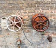 Industriële waterkleppen aan kant van oude fabriek Stock Foto's