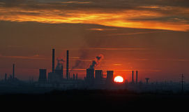 Industriële zonsondergang met fabriekssilhouet Stock Foto's