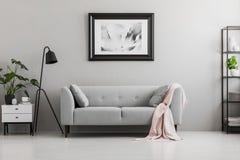 Industriële zwarte staande lamp en een roze deken op een elegante sofa met kussens in een grijs woonkamerbinnenland met plaats vo stock foto