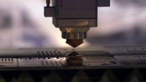 Industri?le lasersnijder met vonken De geprogrammeerde robot hoofdbesnoeiingen met de hulp van een reusachtig blad van metaaltemp stock footage