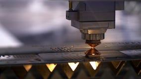 Industri?le lasersnijder met vonken De geprogrammeerde robot hoofdbesnoeiingen met de hulp van een reusachtig blad van metaaltemp stock video