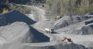 Industri?le stortplaatsvrachtwagens in een steengroeve, de beweging van zware machines in een granietsteengroeve stock footage