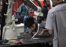 Industri?le technicus die robotachtig lassenwapen in werking stellen stock afbeelding