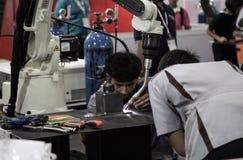 Industri?le technicus die robotachtig lassenwapen in werking stellen stock foto's