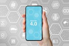 industri 4 0 text som visas på smartphoneskärmen Handen som rymmer modernt frameless, ilar telefonen som är främst av neutral bak Arkivbilder