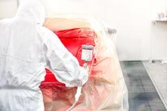 Industria del automóvil - pintor del coche que pinta un coche rojo Fotos de archivo libres de regalías