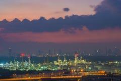 Industria della raffineria di petrolio con il fondo crepuscolare del cielo di paesaggio urbano, sedere Fotografia Stock