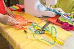 Industria di indumento, adattante concetto seduta della cucitrice della donna fotografie stock