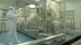 Industria farmaceutica Operaio maschio che ispeziona qualità delle pillole che imballano nella fabbrica farmaceutica automatico stock footage
