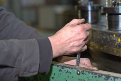 Industria metalúrgica: trabajador del hombre de la fábrica en el uniforme que trabaja en la máquina del torno en taller Foto de archivo libre de regalías